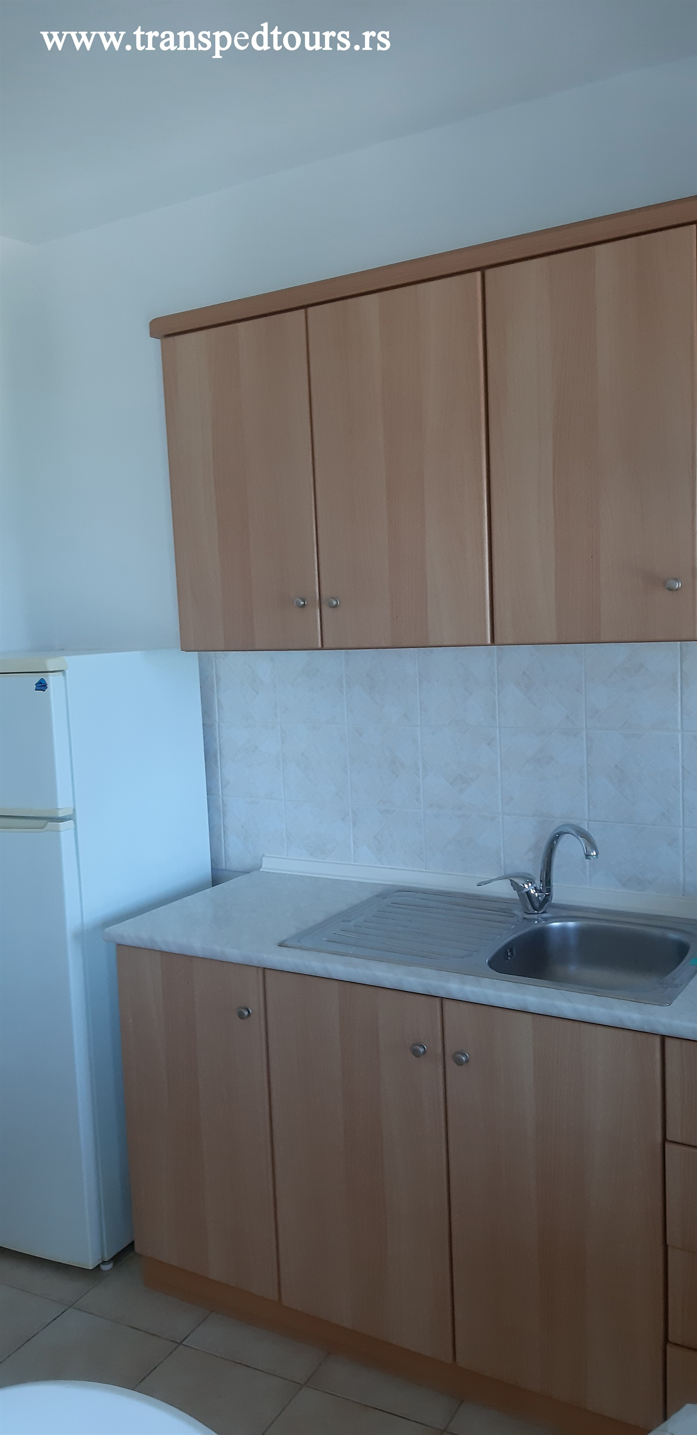 Trokrevetni apartmani se nalaze na prvom spratu u čeonom delu kuće i sastoje se od odvojene kuhinje (šporet sa ravnom pločom i rernom, veliki frižider i potrebno posuđe) sa stolom za ručavanje i spavaće sobe sa dva ležaja (francuski i singl), kupatila i terase na koju se izlazi iz kuhinje i iz spavaće sobe.